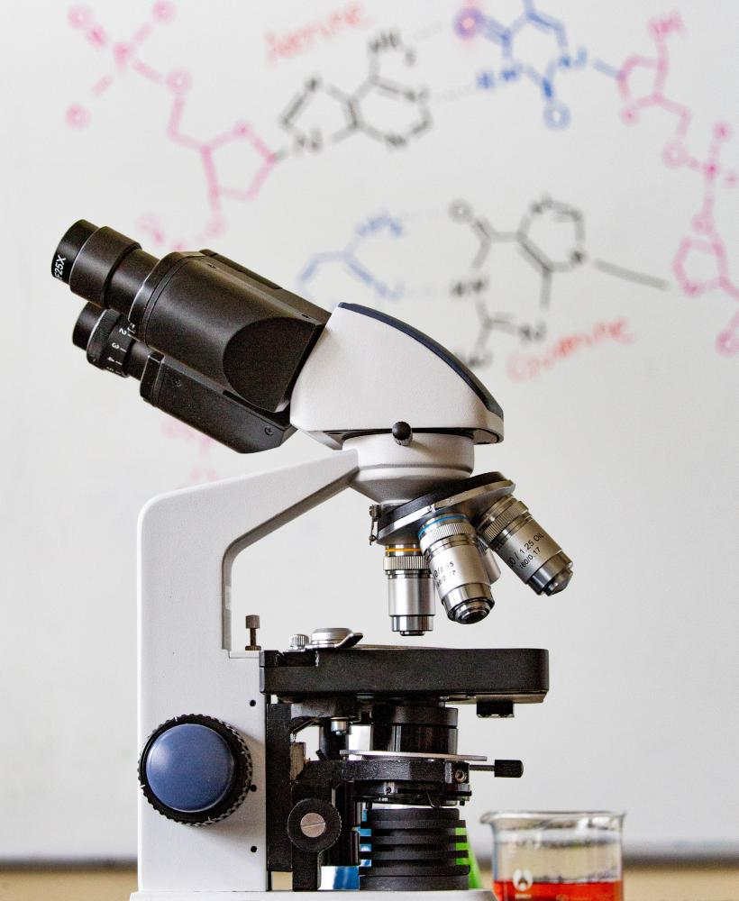 A microscope sits in front of a whiteboard with molecular formulas written on it in various colors of ink.