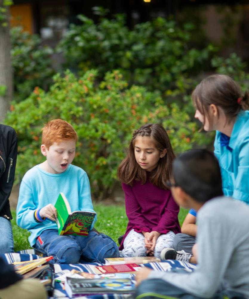 "A group of elementary school students sitting outside on a blanket in circle surrounded by books. A red-haired boy in blue shirt is reading aloud from ""The Wizard of Oz"""