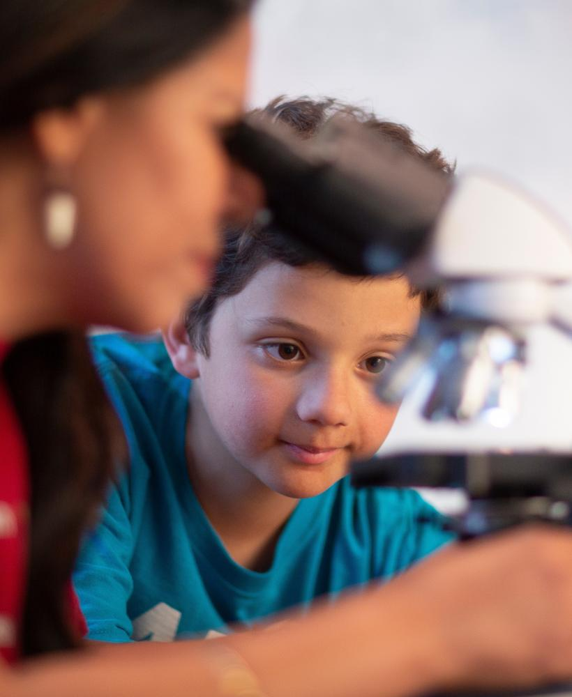 A young boy wearing a blue shirt waits for his turn to use a microscope while his teacher demonstrates how to use it.